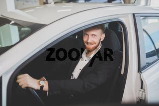 Man examining new car in auto showroom.