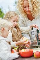 Mutter und zwei Kinder reiben Äpfel