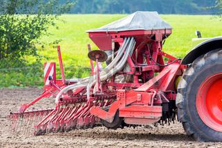 Tractor with agricultural machine on farmland
