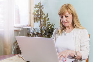 Elderly lady using her personal computer to browse internet
