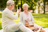 senior couple taking picture by smartphone at park