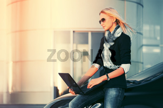 Young fashion business woman with laptop sitting on her car