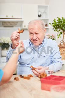 Senior trainiert Gedächtnis mit Puzzle