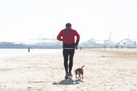 Senior Man Exercising On Beach With His Dog Running Next To Him.
