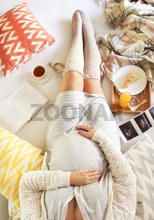 Pregnant woman with book, tea, cake relaxing at home