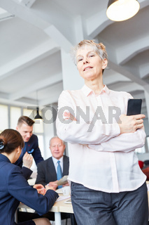 Ältere selbstbewusste Geschäftsfrau im Meeting