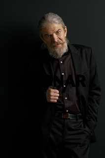 Elderly stylish man standing in studio against black background.