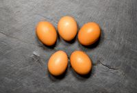 Pattern of eggs on rustic slate table for Easter