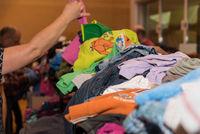 Wühlen nach günstiger Kleidung bei einem Kinderwarenbasar
