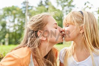 Mutter und Tochter küssen sich liebevoll