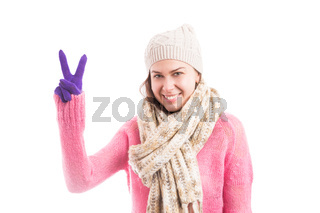 Woman wearing winter season clothes showing peace gesture