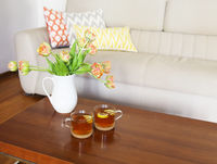 Beautiful orange tulips bouquet on wooden table in the living room