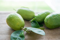 organic green lemons on wood background