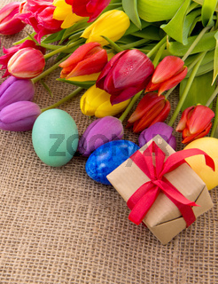Spring tulips with colorful easter eggs and gift box.