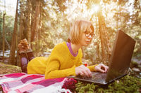 Toned image of a freelancer girl portrait in a yellow sweater and glasses looking thoughtfully at the laptop screen in the nature in a coniferous forest. The concept of freelancing freedom for travel and lack of binding to the office. A laptop lies on the