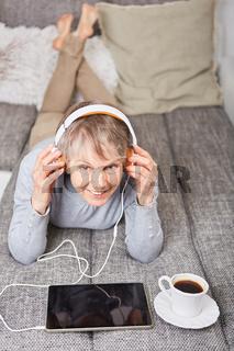 Seniorin hört entspannt Literatur mit Ebook