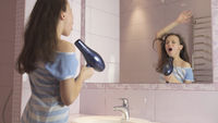 Beautiful happy girl teenager dries hair with hair dryer and sings and dances in front of a mirror in the bathroom