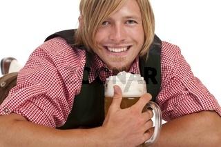 Glücklich Mann liegt am Boden und hält Oktoberfest Maß Bier