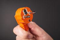 Hand mit orangenem Stecker
