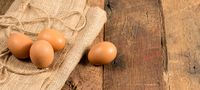 Freshly laid organic eggs on wooden bench