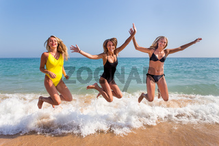 Three girls jumping on beach near sea