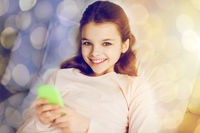 happy girl in bed with smartphone over lights