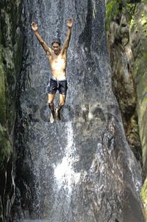 Kleiner junge badet in einem fluss auf phuket, thailand