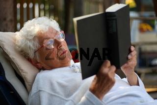 Alte Frau liest Buch im Garten