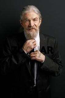 Beardy old man wearing business suit.