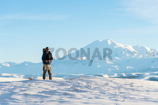 A traveler with a large backpack on his shoulders Stand on a snow-capped hill against the blue sky and the sleeping Elbrus volcano surrounded by the main Caucasian ridge and meditates.