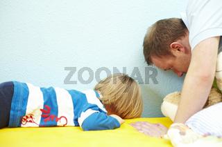 Junge sucht mit seinem Vater hinter dem Bett
