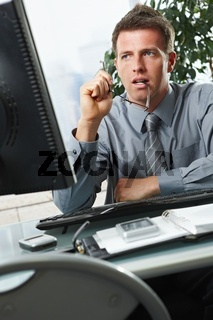 Businessman looking at screen in office