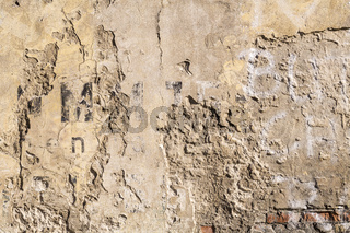 old wall with breaking plaster and vintage letters for backgrounds