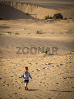 Little boy walking on the sand dunes