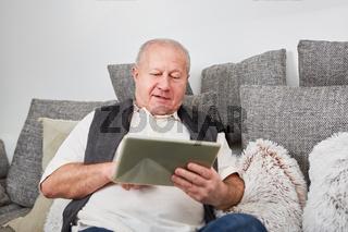 Senior mit Tablet PC chattet entspannt