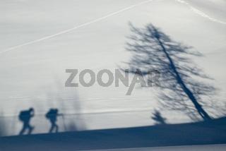 Schatten zweier Wanderer im Schnee