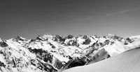 Black and white panorama of snow-capped mountains and off-piste snowy slope