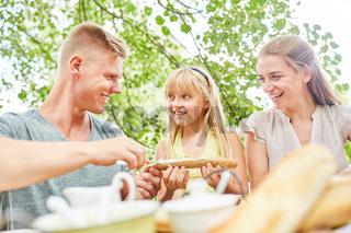 Mädchen und Eltern beim frühstücken
