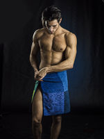 Naked muscular man covering crotch with towel