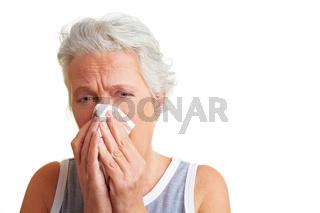Seniorin schnaubt sich die Nase