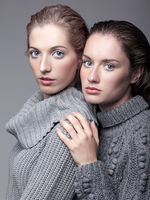 Two young women in gray sweaters on grey background. Beautiful girls stretching hands forward in embrace. Female friendship concept