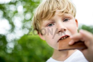 Kind beißt von einem Keks ab