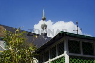 Schieferdach einer Kirche und alte Laube