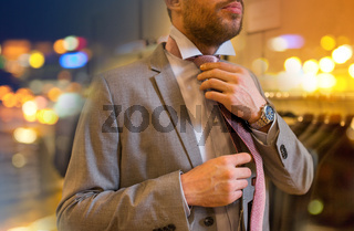 close up of man tying tie at clothing store