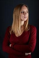 Junge schöne blonde Frau mit verschränkten Armen