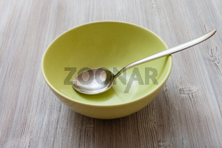 green bowl with steel spoon on gray brown table
