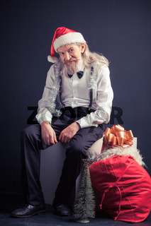 Old tired Santa sitting on chair with gift bag nearby.