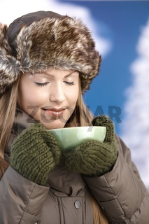 Young female dressed warm enjoying hot tea