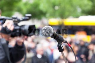 Microphone in focus against blurred crowd. Filming street protest.
