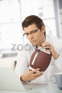 Businessman concentrating on work, holding football